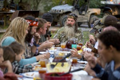 "Phil Robertson heads the family dinner in an episode of ""Duck Dynasty."""