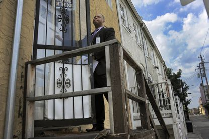 The Rev. Leroy Fitts stands outside his home, May 9, 2014, which is next to a home (back left) where another murder had been committed.