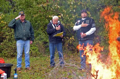 Mike Wellington, Joe Toma and Julian Ordaz stand at attention as they recite the Pledge of Allegiance during an NFL jersey burning ceremony to protest the National Anthem controversy Nov. 12 in Aurora, Ill.