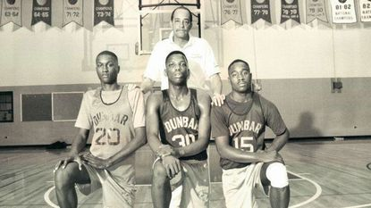 Former Dunbar coach Pete Pompey stands behind players (from left) Donta Bright, Keith Booth and Mike Lloyd in 1991.