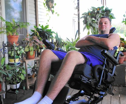 Mickey Chrobot sits in his wheelchair in his home where he grew up, in Taylorsville, Aug. 7. _- Original Credit: Natalie Eastwood/Staff photo