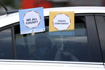 Two young children hold signs through the car window that make reference to the 2020 U.S. census as they wait in the car with their family at an outreach event in Dallas in this July file photo. Maryland advocates are using food distribution events, Instagram and other unconventional means to encourage people to fill out census forms. (AP Photo/Tony Gutierrez, File)
