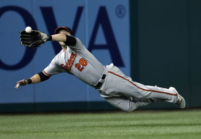 Baltimore Orioles left fielder Steve Pearce dives to catch a ball hit by Washington Nationals' Daniel Murphy during the fourth inning of a baseball game at Nationals Park Thursday, Aug. 25, 2016, in Washington.