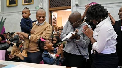 Jerry Haskins watches as his daughter, Sage Harris, 4, celebrates her adoption with her mother, Dawnyell Harris, and sister, Kristyana Harris, 14. They are among the families who took part in an adoption ceremony at the Clarence M. Mitchell, Jr. Courthouse on National Adoption Day last month.