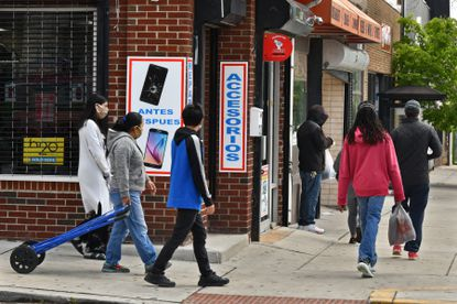 Pedestrians walk along a busy commercial stretch of Eastern Avenue and Eaton Street in southeast Baltimore, a neighborhood with a substantial Latino population. There is a higher incidence of coronavirus in the Latino community. May 11, 2020