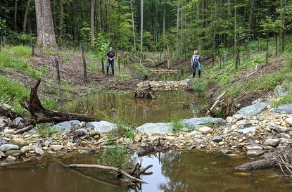 Gravely resident Lara Mulvaney and Arundel Rivers Federation Executive Director Denise Swol walk through a nearly-complete stream restoration project on King's Branch in Davidsonville, in the Gravely neighborhood.