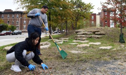 Volunteers Phuong Nguyen, left, and Waldis Cruz, who are Towson University students, rake leaves and pull weeds as part of the clean up the Reservoir Hill neighborhood on Fall Cleanup Day. October 26, 2019