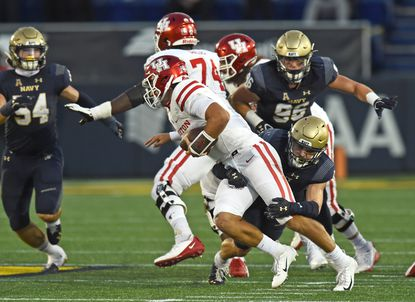 Houston quarterback Clayton Tune, shown being sacked by Navy outside linebacker John Marshall during last season's meeting, leads an offense that is averaging 34.3 points and 329.7 yards through three games this season.