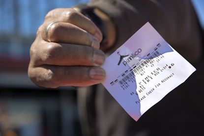 Theodore Robb of Owings Mills holds his winning ticket for the sixth race during Derby Day at Pimlico Race Course Sat., May 1, 2021.(Karl Merton Ferron/Baltimore Sun Staff)