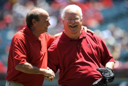 Dr. Lewis Yocum, right, shakes hands with former Los Angeles Angels pitcher Geoff Zahn before throwing out the ceremonial first pitch before the start of a game in August 2011.