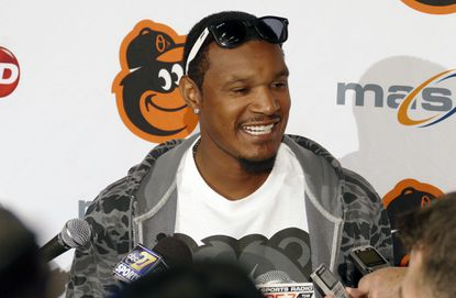 Baltimore Orioles outfielder Adam Jones is surrounded by recording devices, eager to capture his thoughts as he fields reporters' questions, at Orioles FanFest 2015 at the Baltimore Convention Center.