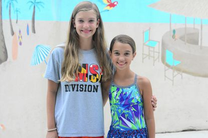 Hayley Sciubba, 12, left, and her sister, Camryn, pose on the deck of Padonia Park Club pool. The sisters are among the young athletes on the club's swim team who say they are looking forward to watching their swimming heroes compete in the Olympic Games.
