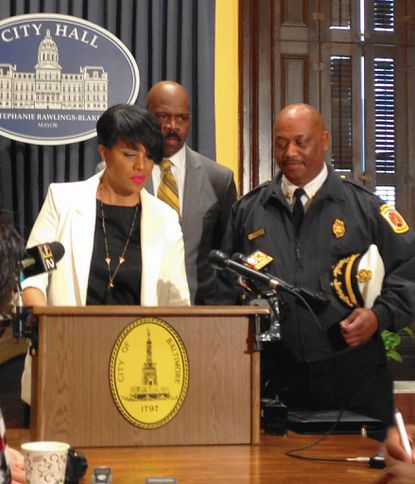 Mayor Stephanie Rawlings-Blake answers questions at City Hall as CitiStat Director Mark Grimes, center, and Fire Chief Niles Ford look on.