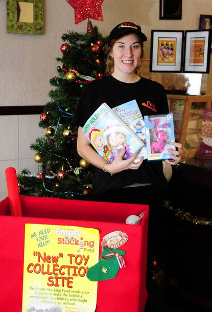 Heather Hren represents the Pat's Pizza Bel Air location presenting the donation of toys collected at the store in the Del Plaza in Bel AIr for the Empty Stocking Fund.