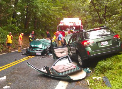 Rescuers look over one of the vehicles involved in an accident on Route 161 south of Darlington on Tuesday morning.