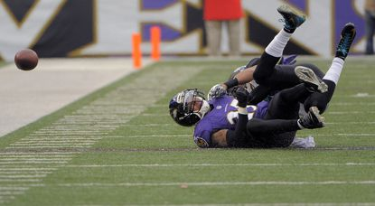 Ravens cornerback Asa Jackson winces as Jacksonville Jaguars wide receiver Cecil Shorts tumbles over him, drawing a foul for offensive pass interference and injuring Jackson during the third quarter.