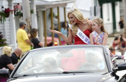 Miss Maryland, Kathleen Masek, of Westminster, waves to parade-goers along with Emma Bonsall, 7, during the Manchester fire company carnival parade along York Street Wednesday, July 5, 2017.