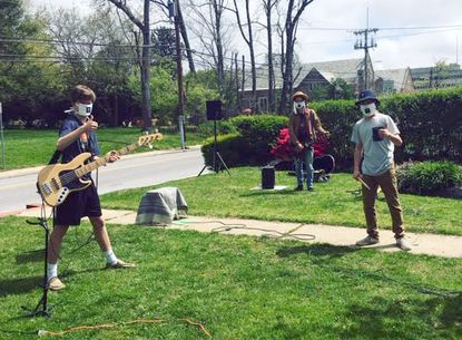 From left, Henry Weetenkamp, Josh Weber and Reed Spaulding prepare to perform a socially distant front-yard concert April 25 in West Towson.