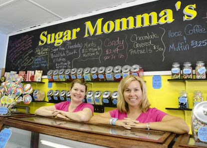 Anne Arundel County resident Amanda Sinclai, left, and Catonsville resident Brandy Benhayon show off some of the treats available at Sugar Momma's, a candy and baked goods shop that the high school friends recently opened on Frederick Road.