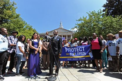 Dr. Heber Brown, III, center, pastor of Pleasant Hope Baptist Church in Baltimore, speaks out against police violence during a news conference by several activist groups at Lawyer's Mall outside the State House to demand statewide reform of police department misconducts.