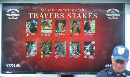 "An official stands near a video board displaying post positions during the Travers Stakes Race Draw at the Druthers Brewery, Tuesday, Aug. 25, 2015, in Saratoga Springs, N.Y. Trainer Bob Baffert says American Pharoah ""looks great"" two days before the Triple Crown winner is scheduled to leave California and arrive at Saratoga Race Course for Saturday's Travers Stakes. (Steve Jacobs/The Post-Star via AP) MANDATORY CREDIT ORG XMIT: NYGLE303"