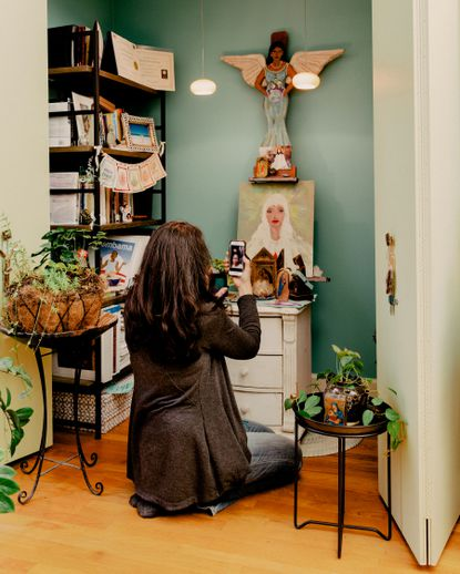 """Susan Pannier-Cass, a spiritual director and ordained minister, kneels at an altar in her home in Chicago, Dec. 11, 2020. Nondenominational """"spiritual companions"""" like Pannier-Cass offer to connect clients to the divine in their everyday life."""