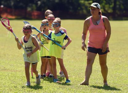 Lacrosse instructor Jackie Parks works with a group of young girls as they practice shooting drills during the Harford Lacrosse Camp at Rocks State Park on Tuesday, July 21.