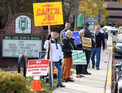 Candidates and campaign volunteers stand along the sidewalk campaigning as voters make their to the polls to vote in the Bel Air Town election Tuesday morning at Town Hall in Bel Air.
