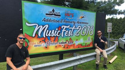 Jesse Tomlin and Brian McCall pose with the poster for the 2018 Addiction & Recovery Awareness MusicFest at the Carroll County Agriculture Center