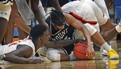 Morgan's Malik Miller, left, fights for the loose ball against Mount St. Mary's Damian Chong Qui in the second half. Mount St. Mary's defeated Morgan State by score of 62 to 54 in men's basketball season opener.