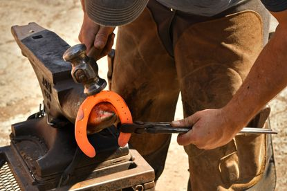 With a rounding hammer, farrier Sean Losee of Mount Airy shapes a heated horseshoe on his anvil for a custom fit.
