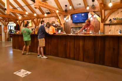 Bartender Kevin Dezell, right, chats with customers in the tap room at Hopkins Farm Brewery, which opened in July.