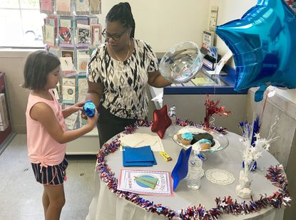 Aberdeen Postmaster Priscilla Burrell gives a cupcake to 9-year-old Lucia Gionfriddo, of West Chester, Pennsylvania as Lucia and her mother visited the Aberdeen post office Saturday during the U.S. Postal Service's 'Customer Appreciation Day.'