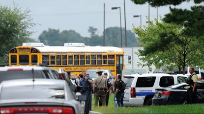 A school bus makes its way to the recent Rite Aid shooting. They were to transport survivors, but Harford school leaders have been asked why they aren't teaching students how to react in a shooting.