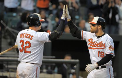 Catcher Matt Wieters, left, gives a high-five to Chris Davis after Davis hit his second home runto help the Orioles beat the New York Yankees in the final game of the 2015 season at Oriole Park. Wieters and Davis were widely expected to leave the team as free agents, but both will be back in 2016, as will Darren O'Day, after the three signed deals totaling $207.8 million this offseason.