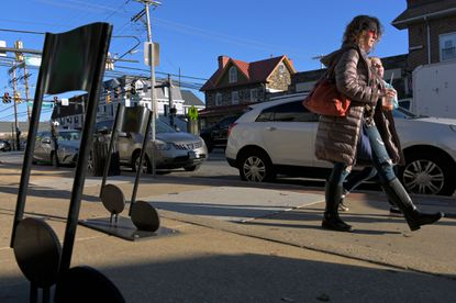 Metal music notes bolted into the sidewalk frame Catonsville native Justine Stull, who now lives in Mt. Airy, and her daughter Clara Stull, 13 on Frederick Road in Catonsville's business corridor Sat., Nov. 16, 2019. (Karl Merton Ferron/Baltimore Sun Staff)
