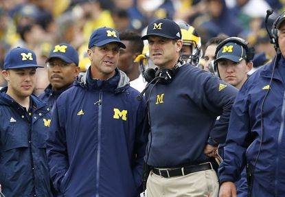 Baltimore Ravens head coach John Harbaugh, second from left, speaks with his brother, Michigan head coach Jim Harbaugh, on the sideline in the second half of an NCAA college football game against Maryland, Saturday, Oct. 3, 2015, in College Park, Md.