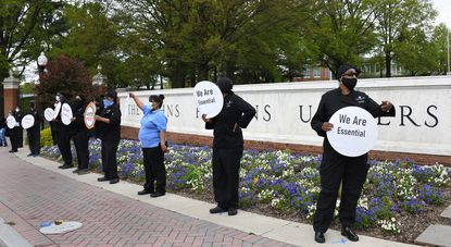 """Johns Hopkins University food service workers from Unite Here Local 7 staged an action earlier this month with social distancing to protest that financial relief pay which was promised by the university has not materialized yet. The workers held signs saying """"We Are Essential."""""""