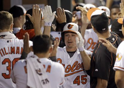 Orioles' Steve Clevenger (45), a Baltimore native, high-fives teammates in the dugout after hitting a three-run home run in the fourth inning against the Oakland Athletics, Monday, Aug. 17, 2015, in Baltimore. Baltimore won, 4-2.