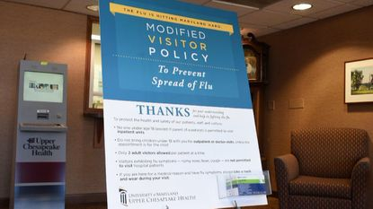 A large sign in the lobby area of the main entrance of the Harford Memorial Hospital in Havre de Grace explains the hospital's recent policy to help prevent the spread of the flu virus.