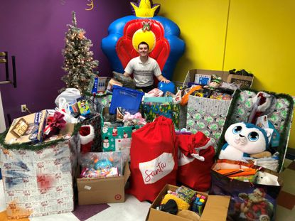 Tobias Liska is surrounded by items from one of the toy drives he organizes to benefit children in need.