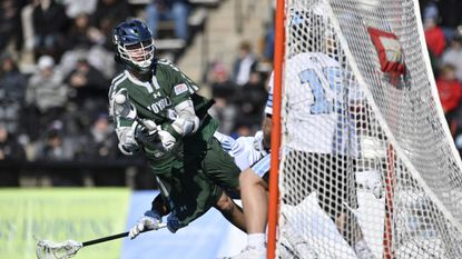 Loyola Maryland's Chase Scanlan dives to score his first goal past Johns Hopkins goalkeeper Ryan Darby in the Greyhounds' 18-12 victory over the Blue Jays at Homewood Field in 2019.