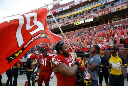 Maryland offensive lineman Ellis McKennie waves a flag in remembrance of offensive lineman Jordan McNair.