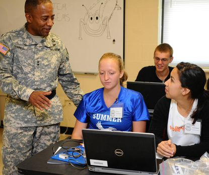Aberdeen Proving Ground commander Major General Robert S. Ferrell, left, speaks with students Valeria Laryoshyna, left, and Kelly Szianiawski, right about their project during Tuesday's STEM and Education Outreach Center opening at the post.
