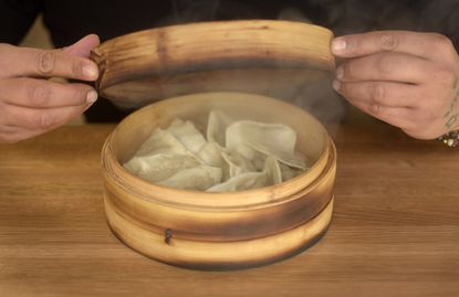 "Tim ""Chyno"" Chin takes the lid off steamed dumplings at Pinch in the Mount Vernon Marketplace. The food hall stall is offering a 50 percent discount to federal employees during the shutdown."