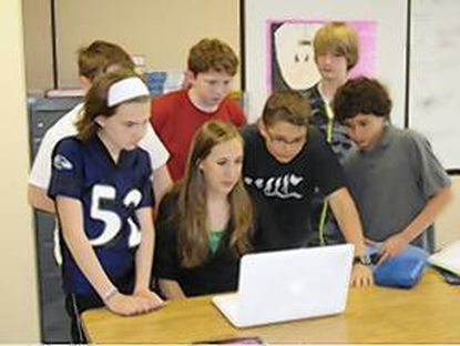 Seventh grade students, with teacher Lauren Redding, view the latest video from Afghanistan.