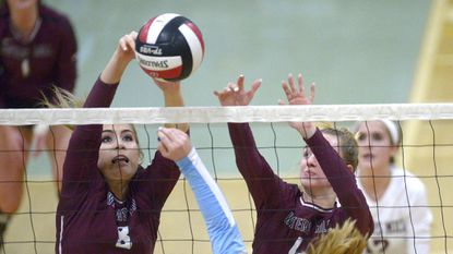 Winters Mill's Kristin Vaeth and Megan Ruff meet Westminster's Emily Bartlett at the net during the second set of their match in Westminster Thursday, Oct. 18, 2018.