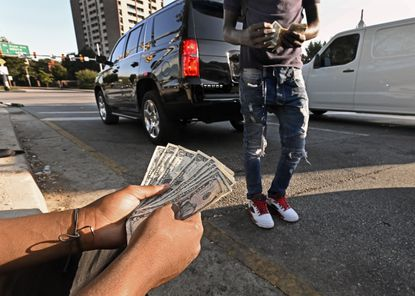 """Baltimore City youths work for tips washing windshields as cars stop for the red light at the I-83 exit on North Avenue. City officials and non-profit partners are trying to work on a new, more holistic approach to help the """"squeegee kids"""" move from the street into other jobs."""