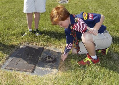 Webelos Scout Reid Bycoffe places an American flag on veteran's grave.