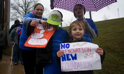 Dayana Bergman,left, hands her son Angelo a sign, while Ashton Bergman holds up another sign and Aven Bergman holds in umbrella. Bergman was at a rally outside Lansdowne High School Feb. 23 2016 supporting calls for a new building.